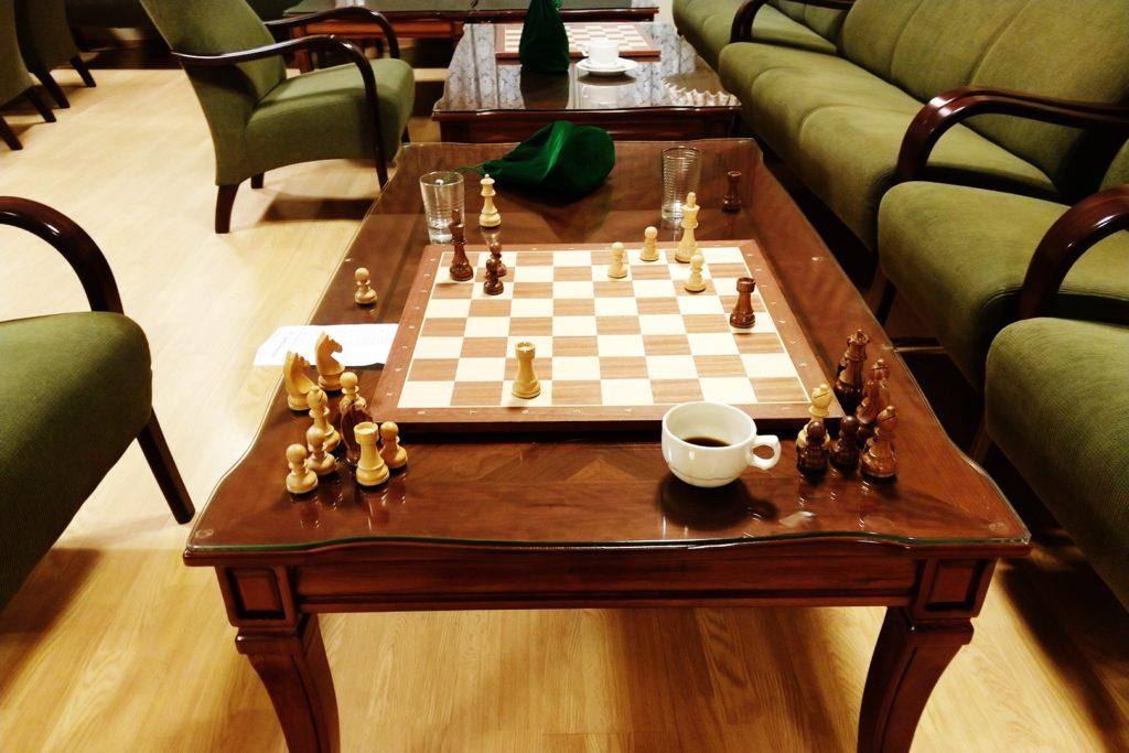 Sjakkbrett og kaffekopp på bord